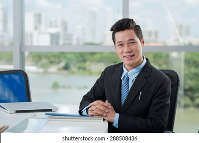 Portrait of Vietnamese middle-aged businessman smiling and looking at the camera