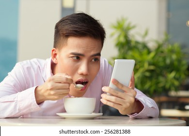 Portrait of Vietnamese young man addicted to smartphone