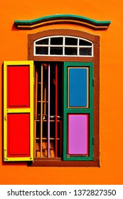 Portrait view of colorful traditional Indian window with antique shutters in an orange wall of a vintage shop house in Little India, Singapore.