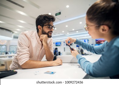 Portrait view of curious excited happy smiling young student bearded man looking at mobile while female seller giving instruction for sim place on the phone after buying with bank card in a tech store