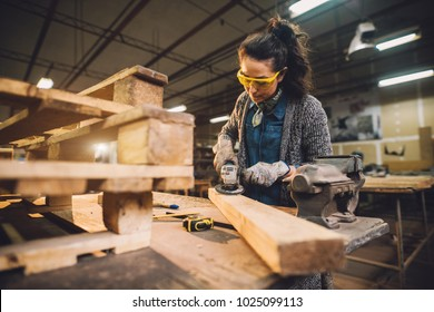 Portrait view of hardworking middle aged professional female carpenter worker working with sandpaper and choosing wood in the workshop.
