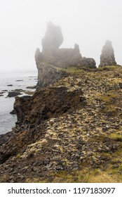 Portrait view of Londrangar, Iceland on a Foggy day showing the cliffs and coastline.
