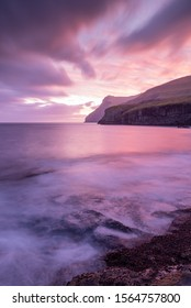 A portrait view of a mauve cloud and sunrise explosion, the smooth waves gliding into the rocky coastline of Eidi in the Faroe Islands.