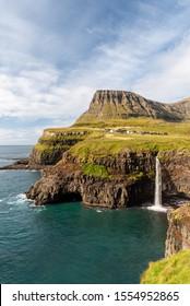 Portrait view of Mulafossur Waterfall and surrounding coastline from afar. Gasadalur, Faroe Islands. September 2019.