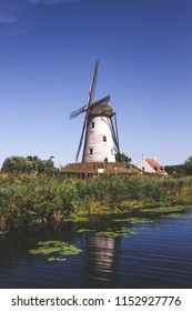 """portrait view of an old windmill in the small town of """"Damme"""" in northern Belgium, with a river and vegetation in the foreground"""