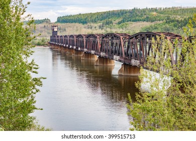 A portrait view of a rusty railway bridge across the Fraser River in British Columbia
