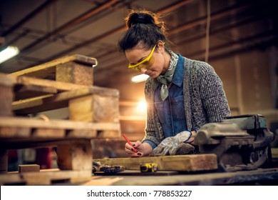 Portrait view of satisfied smiling middle aged professional female carpentry worker with a pencil drawing on the wood and tape measure, steel vise on the table in the workshop.