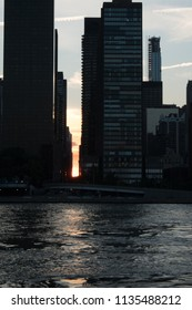 Portrait view of sun setting during Manattanhendge and the East River as sun sets perfectly between New York City skyscrapers and dusk, reflection of buildings on the East River at sunset in NYC.