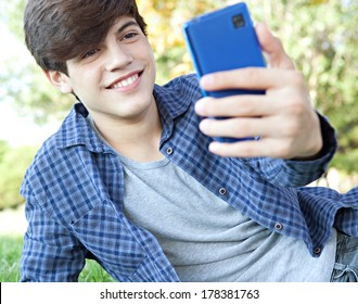 Portrait view of a teenager student boy laying down in a park with his college books, using a smartphone to take a selfie photo of himself for networking, posing and smiling. Technology lifestyle.