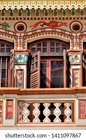 Portrait view of traditional vintage Peranakan or Straits Chinese Singapore shop house with arched window, antique brown wooden shutters and ornate columns in historic Little India