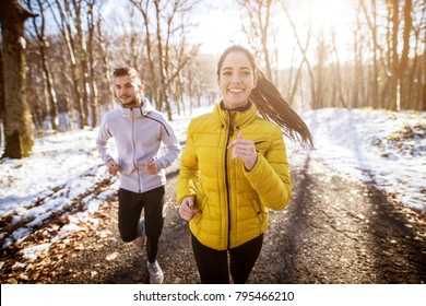 Portrait view of young happy cute charming adorable fitness shape girl in winter sportswear jogging in the snowy forest with her boyfriend or trainer.