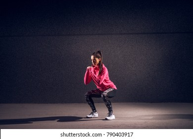 Portrait view of young sexy attractive healthy fitness sporty active slim girl with sportswear crouching and doing squats while holding hands together in front of the grey wall at night on the street.