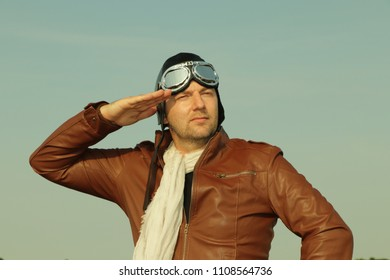 Portrait of a vintage pilot with leather cap, scarf and aviator glasses salutes - Portrait of a man in historical pilot clothing