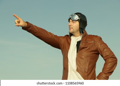 Portrait of a vintage pilot with leather cap, scarf and aviator glasses points to something in the sky - Portrait of a man in historical pilot clothing