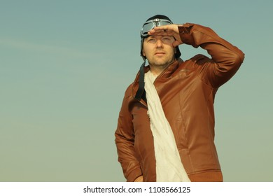 Portrait of a vintage pilot with leather cap, scarf and aviator glasses looks into the distance - Portrait of a man in historical pilot clothing