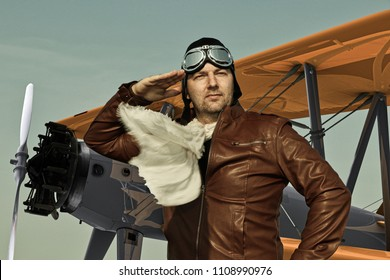 Portrait of a vintage pilot with leather cap, scarf and aviator glasses salutes in front of a historic airplane - Portrait of a man in historical pilot clothing