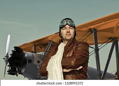 Portrait of a vintage pilot with leather cap, scarf and aviator glasses in front of a historic airplane biplane - Portrait of a man in historical pilot clothing