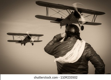 Portrait of a vintage pilot with leather cap, scarf and aviator glasses in front of a flying historical biplane - Portrait of a man in historical pilot clothing - vintage old picture style