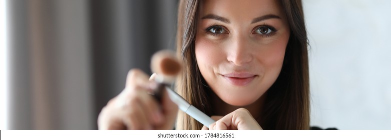 Portrait of visagist looking at camera with shyness and gladness. Smiling make-up artist using special and professional tools. Beauty and maquillage concept