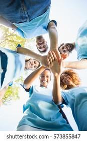 Portrait of volunteer group forming huddles in park