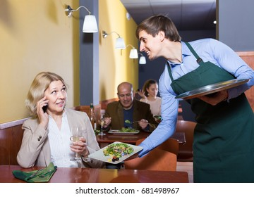Portrait of waiter and ordinary mature woman having dinner