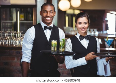 Portrait of waiter and waitress holding a serving tray with glass of cocktail
