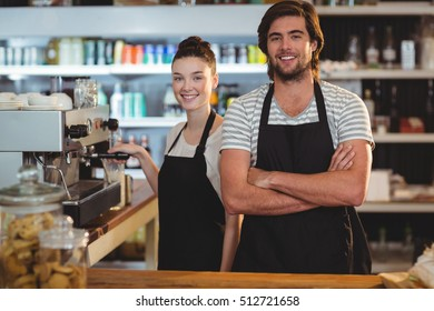 Portrait of waiter and waitress making cup of coffee at counter in cafe