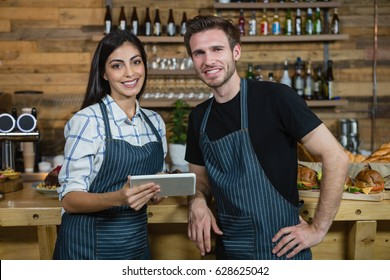 Portrait of waiter and waitresses using digital tablet at counter in café