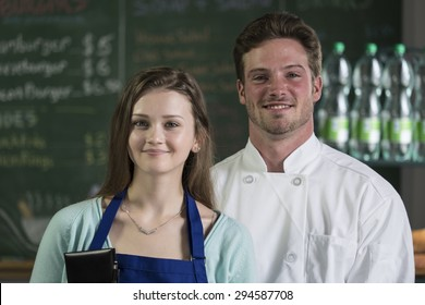 Portrait of a waitress and chef, smiling