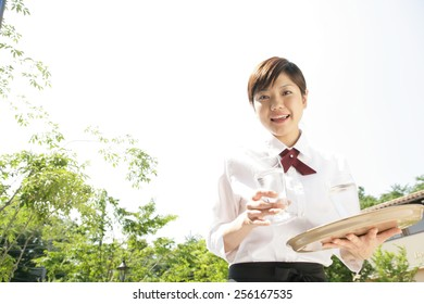 Portrait of a waitress holding two glasses of water and smiling