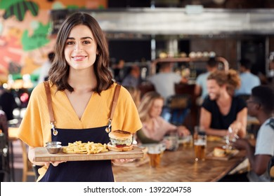 Portrait Of Waitress Serving Food To Customers In Busy Bar Restaurant