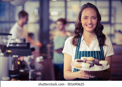 Portrait of a waitress showing a plate of cupcakes at the coffee shop