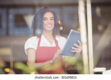 Portrait of a waitress using a digital tablet at the coffee shop
