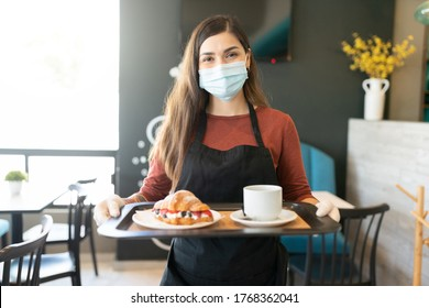 Portrait of waitress wearing face mask while serving order in coffee shop