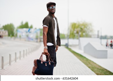 Portrait of walking stylish african american man wear on sunglasses and cap with handbag outdoor. Street fashion black man.