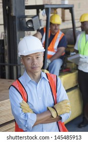 Portrait of warehouse manager with arms crossed and colleagues in background