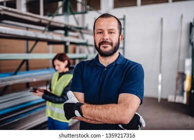 Portrait of warehouse worker looking at camera with female warehouse clerk standing behind him