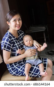 Portrait of a warm relationship between a young little Asian boy baby dresses in grayish clothes sitting on a lap of his own pretty mother with dark wooden wall in background