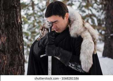portrait of a warrior in black quilted clothes, leather gloves, in a cloak with a fur collar. He sits on his knee and prays, holding a long sword in his hands. winter forest background