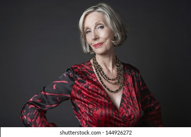 Portrait of a wealthy senior woman wearing necklace against black background