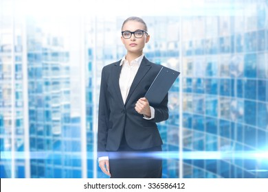 Portrait of wearing glasses businesswoman who hands black folder, blue background. Concept of leadership and success