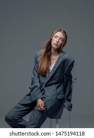 Portrait of weary young beautiful woman in oversized man's suit sitting isolated grey background