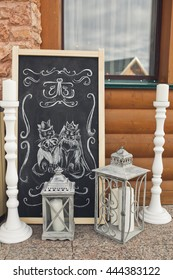 A portrait of wedding cats painted on a black board surrounded with white candles