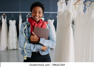 Portrait of wedding dress store owner with a diary. Woman dressmaker in her bridal boutique.