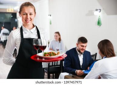 Portrait of welcoming female waiter who is standing in restaurante indoor.