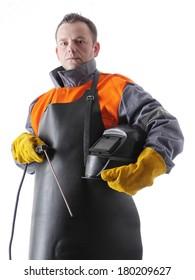 Portrait of welder wearing protective welding black leather apron, welding hood and welding electrode holder over white