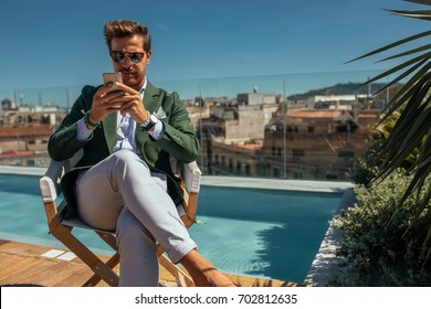 Portrait of a well dressed young man using mobile phone sitting by the pool.