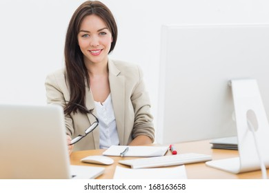 Portrait of a well dressed young woman with computers sitting at desk in the office