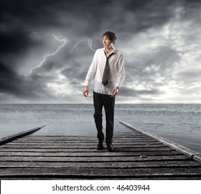 Portrait of a wet businessman walking on a dock looking over the sea with stormy sky on the background