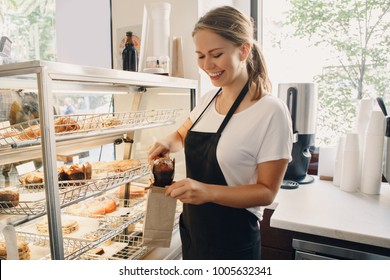 Portrait of white Caucasian beautiful barista woman taking muffin pastry from shop-window. Person at work place small business concept